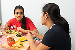 14 year old teenage girl in kitchen with mother, sitting at table, preparing vegetables, talking