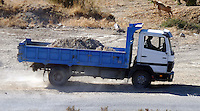 Pictured: The loaded tipper lorry moves soil from the new site to the farmhouse in order to be searched in Kos, Greece. Sunday 09 October 2016<br />