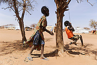 BURKINA FASO Dori , malische Fluechtlinge, vorwiegend Tuaregs, im Fluechtlingslager Goudebo des UN Hilfswerks UNHCR, sie sind vor dem Krieg und islamistischem Terror aus ihrer Heimat in Nordmali geflohen, Kinder schaukeln an einem Baum / BURKINA FASO Dori, malian refugees, mostly Touaregs, in refugee camp Goudebo of UNHCR, they fled due to war and islamist terror in Northern Mali, children swing on tree