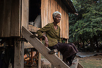 "Cambodia - Kampong Speu Province - Toun Manh, 73, sitting on the staircase of her house in Thnal village. Toun was expropriated of 1,5 hectares of land, and was compensated with just half a hectare. Given her old age, though, she cannot clear the new land for planting rice and is therefore forced to buy it on the market. The mother of 5 kids, Toun survives thanks to the support of her 15-year-old orphaned grandson. ""But if he gets sick one days, how will I manage?"" she asks worried."