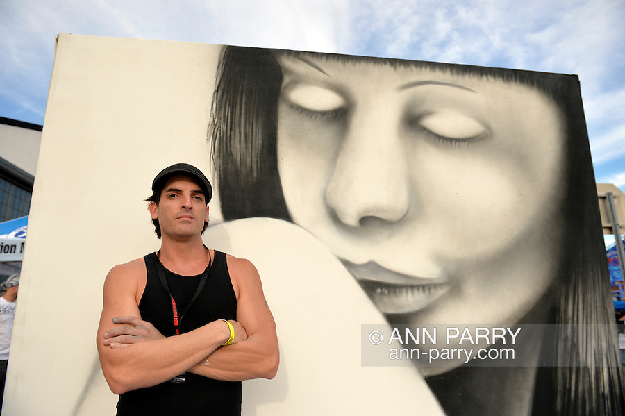 Garden City, New York, USA. September 14, 2014. SEAN GRIFFEN, aka NME, of Freeport, is a graffiti artist creating an outdoor mural of a girl, at the United Ink Flight 914 tattoo convention at the Cradle of Aviation museum of Long Island.
