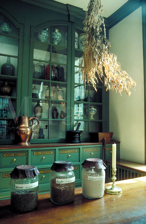 interior view of apothocary at Williamsburg historic site showing shelves with jars and bottles and plants used for medicinal purposes. Williamsburg Virginia USA.