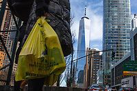 NEW YORK, NY - APRIL 2: A woman carries her groceries on a plastic bag while the World Trade Center is seen on the back ground on April 2, 2019 in New York. New York will become the second state in U.S. to ban shops from providing single-use plastic bags for most purchases.   (Photo by Eduardo MunozAlvarez/VIEWpress)