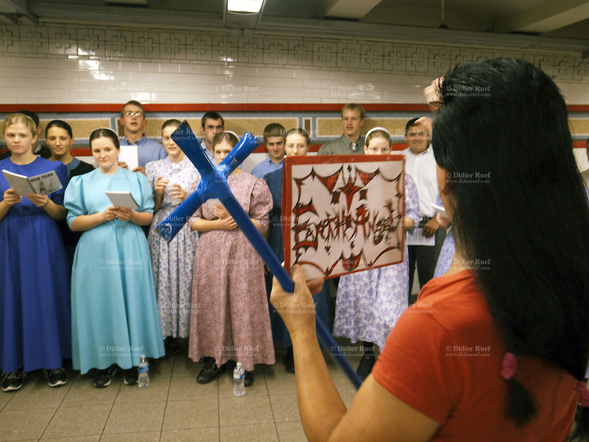 "USA. New York City. Union Square. Subway station. Unexpected religious encounteer betweeen a group of Mennonites singing and proselytizing, and a man calling himself ""The Angel"", who carries a blue catholic cross in his hands. Mosaic tiles on wall. 22.10.2011 © 2011 Didier Ruef"