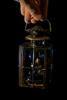 Man's hand holding a burning old-fashioned oil lamp.