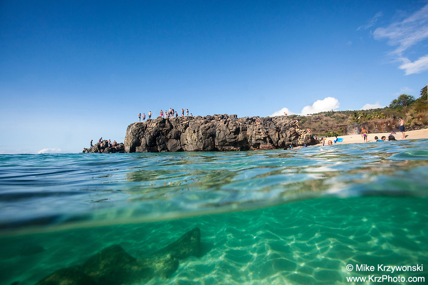 Split-shot view from the ocean of beachgoers standing on top of the famous jump rock at Waimea Bay, Oahu