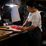 A man prepares tuna under an electric light - more than likely power by nuclear power, at Tsukiji Fish Market is the largest fish market in the world.