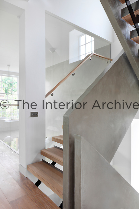 A hallway with a modern staircase with wooden treads. Glass panels allow a view through to a double height ceiling.