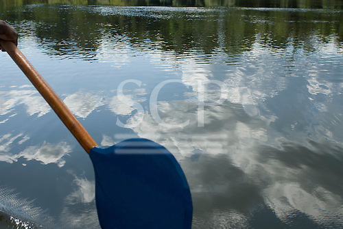 Pará State, Brazil. Xingu River. Blue paddle, reflected clouds.
