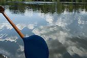 Pará State, Brazil. Xingu River. Blue paddle, reflected clouds.