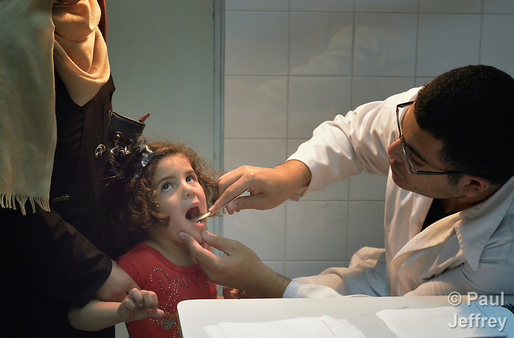 Dr. Khalid Abu Ajwa examines a girl in the Al Ahli Arab Hospital in Gaza City. The Anglican Church-affiliated hospital is a member of the ACT Alliance.<br /> <br /> The 2014 war provoked serious damage to Gaza's health infrastructure. Seventeen hospitals, 56 primary health care facilities and 45 ambulances were damaged or destroyed. Sixteen health care workers were killed and 83, most of them ambulance drivers and volunteers, were injured. <br /> <br /> Parental consent obtained.