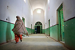 Female election officials walk in a deserted hallway at a women's polling center in Kandahar, Afghanistan, Thursday, Aug. 20, 2009. Fear of Taliban attacks kept many women at home during Afghanistan's presidential and provincial council elections.