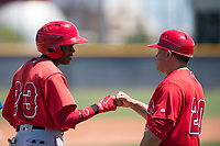 Los Angeles Angels shortstop Daniel Ozoria (23) is congratulated by coach Jack Santora (20) after reaching third base during an Extended Spring Training game against the Chicago Cubs at Sloan Park on April 14, 2018 in Mesa, Arizona. (Zachary Lucy/Four Seam Images)