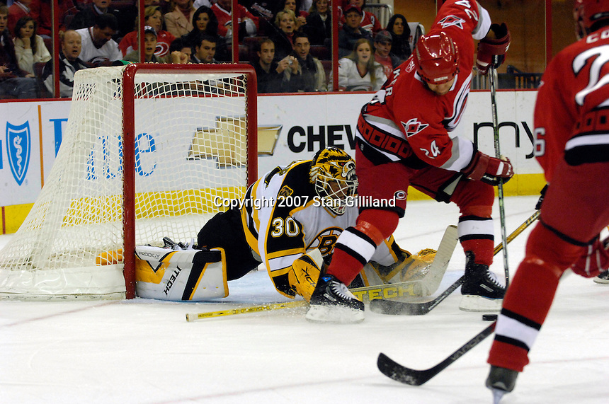 Carolina Hurricanes' Scott Walker (24) tries to get off a shot defended by the Boston Bruins' goalie Tim Thomas (30) Saturday, Feb. 3, 2007 at the RBC Center in Raleigh. Boston won 4-3 in overtime.