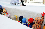 Children line up for a slide in the snow during the snow and ice festival in Sapporo City, northern Japan. About 2 million people visit the city to see the hundreds of hand-crafted snow and ice sculptures that have graced the Sapporo Snow Festival since its inception in 1950.