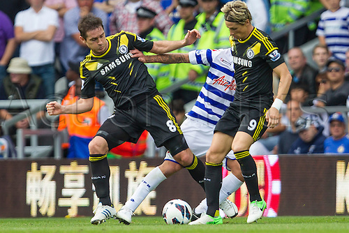 15.09.2012 London, England. Frank Lampard and Fernando Torres tackle Alejandro Faurlín in action during the Premier League game between Queens Park Rangers and Chelsea from Loftus Road.