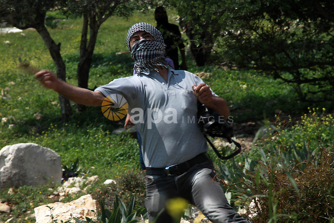 A Palestinian protester throws stones at Israeli security forces following a weekly protest against the expropriation of Palestinian land by Israel in the village of Kfar Qaddum, near Nablus, in the occupied West Bank on March 21, 2014. Photo by Nedal Eshtayah