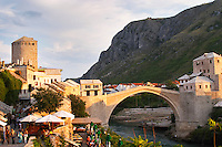 the busy old market bazaar street Kujundziluk with lots of tourist craft and art shops and street merchants. Sunset late afternoon light. View along the river of the old reconstructed bridge. Restaurants cafes along the river bed. Historic town of Mostar. Federation Bosne i Hercegovine. Bosnia Herzegovina, Europe.