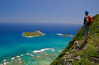 A hiker (man) stops to enjoy a panoramic view of Manana(Rabbit)island,Kaohikaipu island(Blackrock)and Kaupo Bay(Cockroach Bay) from Tom-tom Trail above Sea life park along the windward oahu coast.