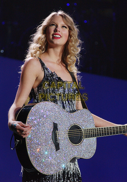 """TAYLOR SWIFT .Country music artist TAYLOR SWIFT performs as headliner of her Sold Out, """"Fearless Tour 2009"""" held at the Quickens Loan Arena, Cleveland, Ohio, USA.  .October 3rd, 2009.stage concert live gig performance music half length silver black dress guitar .CAP/ADM/DS.©Devin Simmons/AdMedia/Capital Pictures."""