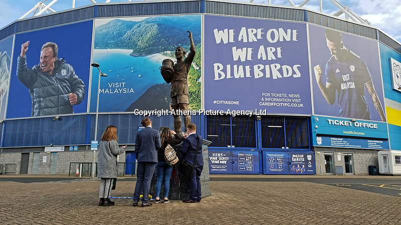 Pictured: People by the statue of Fred Keenor outside the Cardiff City Stadium in south Wales, UK. Tuesday 22 January 2019<br /> Re: Premier League footballer Emiliano Sala was on a flight which disappeared between France and Cardiff.<br /> The Argentine striker was one of two people on board the Piper Malibu, which disappeared off Alderney on Monday night.<br /> Cardiff City FC, signed the 28-year-old from French club Nantes.<br /> A search is under way.<br /> A Cardiff Airport spokeswoman confirmed the aircraft was due to arrive from Nantes but said there were no further details.<br /> HM Coastguard has sent two helicopters to help.