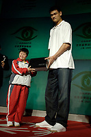 Chinese NBA star Yao Ming presents gifts to a Special Olympics athlete at a Special Olympics event in Beijing Friday July 21, 2006. (photo by Lou Linwei/Sinopix)