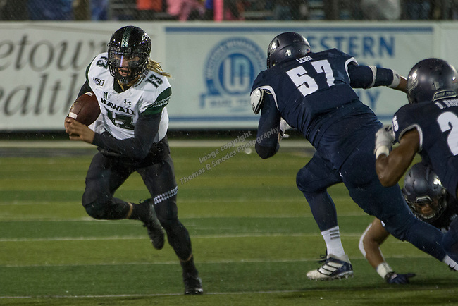 Hawaii quarterback Cole McDonald (13) rolls out as he is rushed by Nevada defensive end Jaden Lewis (57) in the first half of an NCAA college football game in Reno, Nev. Saturday, Sept. 28, 2019. (AP Photo/Tom R. Smedes)