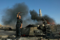 Iraq: Baghdad: August 16, 2004: A militiaman loyal to Shiite cleric Moktada al-Sadr raises his weapon while standing on top on a burning US Army tank after the tank was destroyed during clashes between the Madhi Army and US Forces in Sadr City.