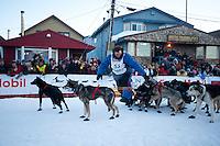 John Baker leads his team across the finish line in Nome.