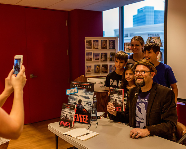July 26, 2017. Raleigh, North Carolina.<br /> <br /> Alan Gratz posed for a photo with (left to right) Daniel, Juliana, Abigail and Talmage Andros. <br /> <br /> Author Alan Gratz spoke about and signed his new book &quot;Refugee&quot; at Quail Ridge Books. The young adult fiction novel contrasts the stories of three refugees from different time periods, a Jewish boy in 1930's Germany , a Cuban girl in 1994 and a Syrian boy in 2015.