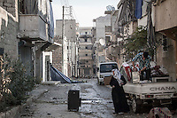 In this Sunday, Dec. 02, 2012 photo, Syrian residents get back to their home in Amarya neighborhood as they collect their belongings after the rebel fighters took control of the area over the Syrian army during heavy fighting in Aleppo, the Syrian's largest city. (AP Photo/Narciso Contreras)