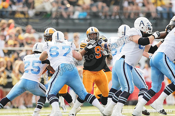 September 7, 2009; Hamilton, ON, CAN; Hamilton Tiger-Cats defensive lineman Demonte' Bolden (90) battles Toronto Argonauts centre Dominic Picard (64). CFL football - the Labour Day Classic - Toronto Argonauts vs. Hamilton Tiger-Cats at Ivor Wynne Stadium. The Tiger-Cats defeated the Argos 34-15. Mandatory Credit: Ron Scheffler.