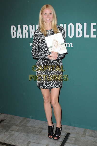 """Gwyneth Paltrow.Gwyneth Paltrow's """"It's All Good: Delicious, Easy Recipes that Will Make You Look Good and Feel Great"""" Book Signing held at Barnes & Noble The Grove, Los Angeles, California, USA..April 3rd, 2013         .full length dress black white pattern print               ankle boots open toe belted .CAP/DVS.©DVS/Capital Pictures."""