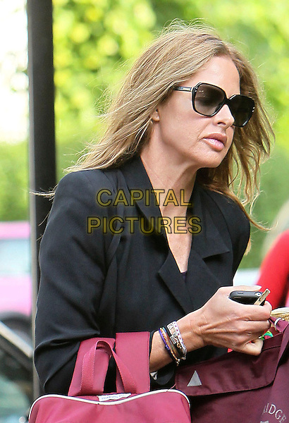 TRINNY WOODALL .pictured in London, England, UK, .May 3rd 2011..half length sunglasses lips plastic cosmetic surgery black blazer jacket  hand side profile bracelets phone .CAP/HIL.©John Hillcoat/Capital Pictures