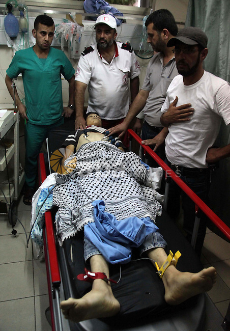 The body of 14-year-old Mohammad Jihad Dodeen is seen at Alia Hospital after reportedly being shot to death by Israeli soldiers in Doura village, in the West Bank town of Hebron, June 20, 2014. In the early morning Israeli soldiers entered Doura village arresting Palestinians during a military search operation. Photo by Mamoun Wazwaz