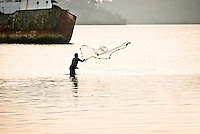 Port Blair, Andaman Islands.  Indian man throwing his cast net to catch mullet or sardines in a very polluted bay