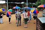 Tourists carrying umbrellas Gal Viharaya, UNESCO World Heritage Site, the ancient city of Polonnaruwa, Sri Lanka