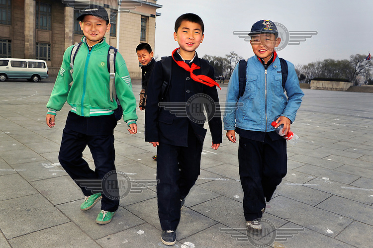 A group of young boys on their way back home walk through.Kim Il-sung Square.
