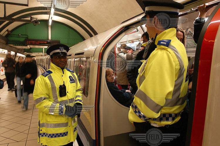 Police officers patrol a London Underground tube station.