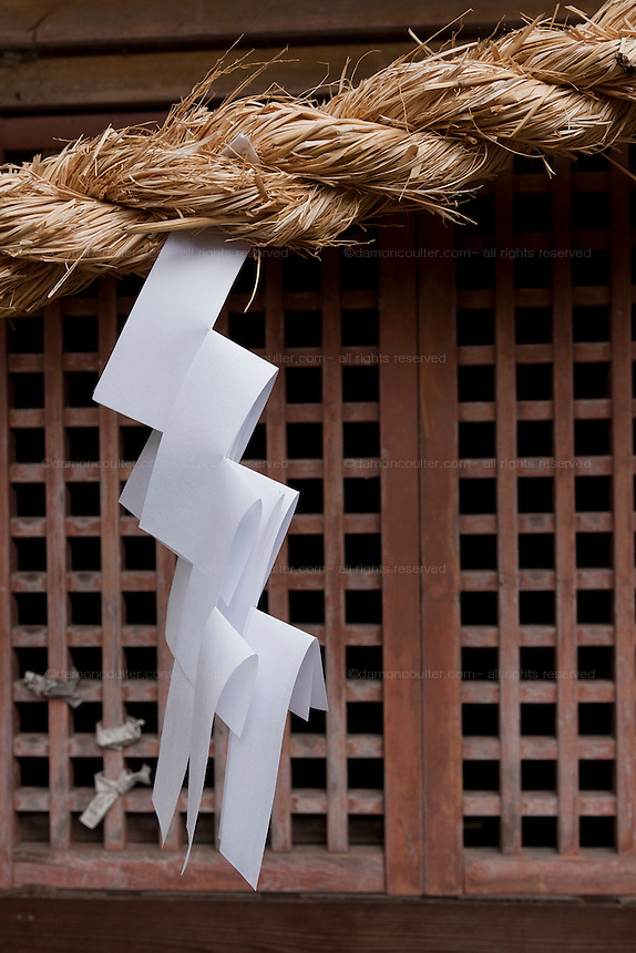 Zig zag, shide paper hanging from a rope across the entrance to a Shinto shrine in Kanazawa, Ishikawa, Japan. Tuesday October 14th 2008