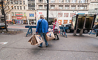 Shoppers loaded up on bargains outside of American Eagle Outfitters in the Herald Square shopping district in New York on Thanksgiving Day, Thursday, November 26, 2015. Many retailers opened their doors on Thanksgiving day including some in Herald Square hoping to capture the dollars from shoppers after the parade. (© Richard B. Levine)