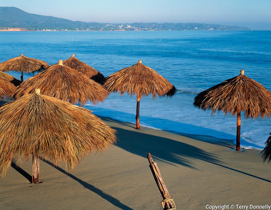 Nayarit, Mexico<br /> Thached Pallapas on the beach in the village of Bucerias with Bahia de Banderas (Banderas Bay) and Punta de Mita in the distance