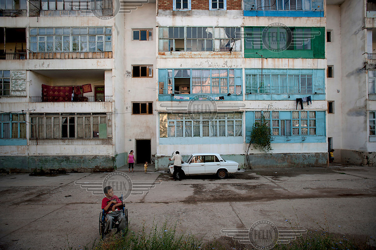 13 year old Anarbek Dolotaliev sits in a wheelchair outside an old Soviet era apartment block where his father, Kalil, is checking the engine of an old Lada car. Anarbek has Arthrogryposis, a neuro-musculo-skeletal disorder that affects various joints in the body. It is a congenital disorder that is non-progressive and in this case the condition has been linked to pollution in Mailuu-Suu....