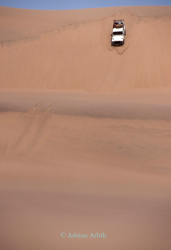 A Land rover  negotiates the sand and sand dunes in the Namib Naukluft desert.  Access is restricted due to Diamond mining activity by DeBeers.