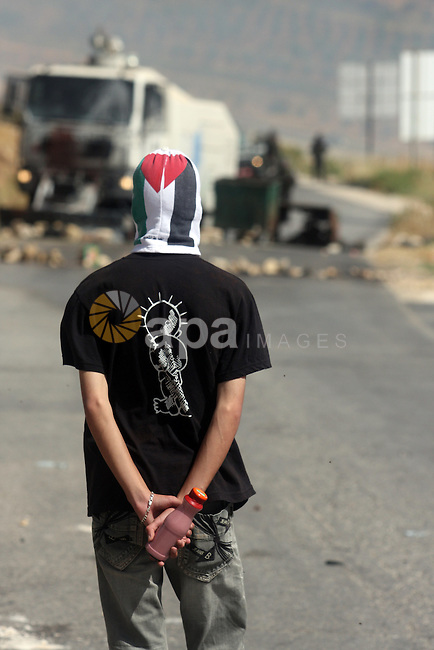 A masked Palestinian protester hurls stones during clashes between stone throwers and Israeli soldiers in the West Bank village of Nabi Saleh, near Ramallah, on May 25, 2012 following a protest against the confiscation of Palestinian land to expand the nearby Jewish settlement of Hallamish. Photo by Issam Rimawi