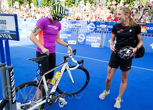 12 JUL 2014 - HAMBURG, GER - Vicky Holland (GBR) (left) from Great Britain and Kirsten Sweetland (CAN) (right) from Canada talk in transition for the start of the elite women's 2014 ITU World Triathlon Series round in the Altstadt Quarter, Hamburg, Germany (PHOTO COPYRIGHT © 2014 NIGEL FARROW, ALL RIGHTS RESERVED)