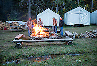 Outdoor Life Editor Andrew McKean, Mike Stock, guide Greg Kriese, and Tim Trefren with Trefren Outfitters talk around a fire after a day of hunting on Greyback Ridge in the Hoeback Drainage of Wyoming Region H, outside of Alpine, Wyoming, September 23, 2015.<br /> <br /> Photo by Matt Nager