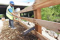 NWA Democrat-Gazette/FLIP PUTTHOFF <br /> GREENWAY FINISHING TOUCH<br /> Carlos Cotte cleans a new wood fence on Tuesday May 14 2019 along the Razorback Greenway in Rogers. New wood fencing and beutification are nearly complete along the Greenway near New Hope Road and Interstate 49.