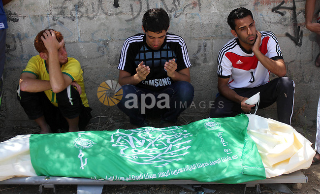 People mourn over the body of a Palestinian man, who medics said was killed in an Israeli shelling, at a street in Gaza City on July 26, 2014. Israeli forces have succeeded in destroying at least 1,900 houses and 22,800 have been partially damaged. Some 46 schools, 56 mosques and seven hospitals had also suffered varying degrees of destruction, as Palestinian death toll topped 1,000 citizen, Palestinian officials. Photo by Alaa Shamaly