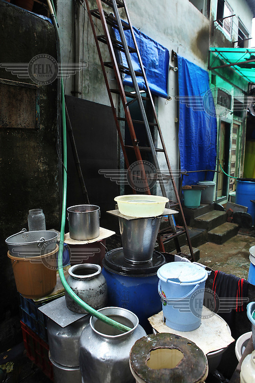 Rainwater harvesting in a slum in Mumbai. During the monsoon rains people try to harvest rainwater by filling all available jars. Access to drinking water in slum areas is poor and slum dwellers often pay a higher price for their water than people living in more affluent areas.